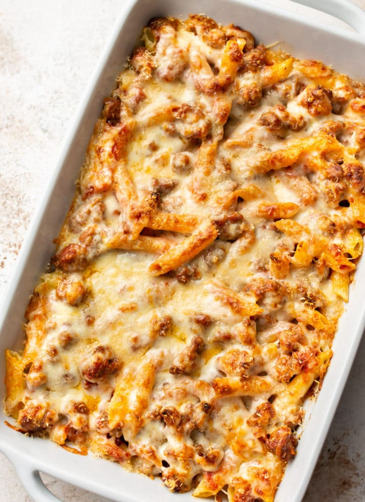 penne pasta bake with sausage in a white 9x13 baking dish
