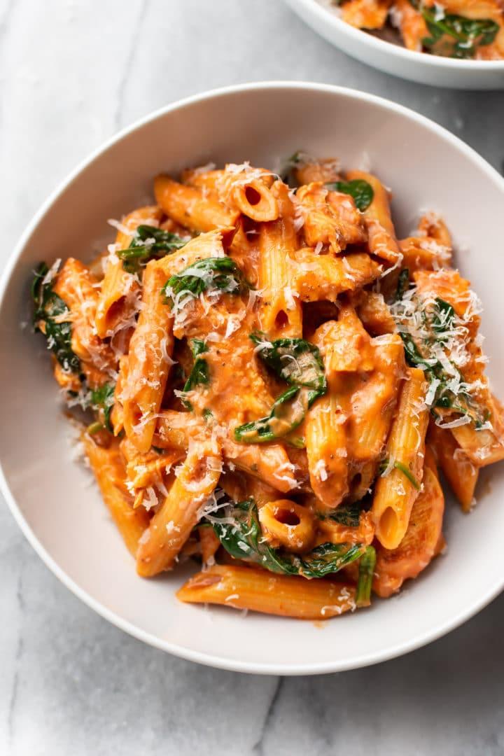 creamy tomato spinach chicken pasta in a white bowl