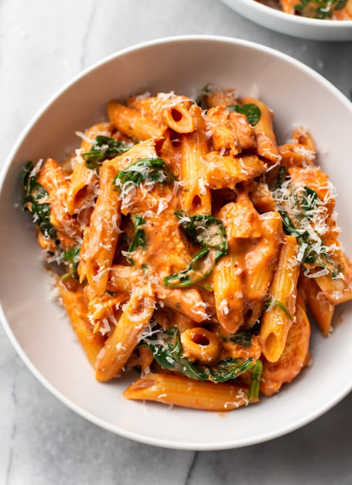 creamy tomato spinach chicken pasta in a white bowl