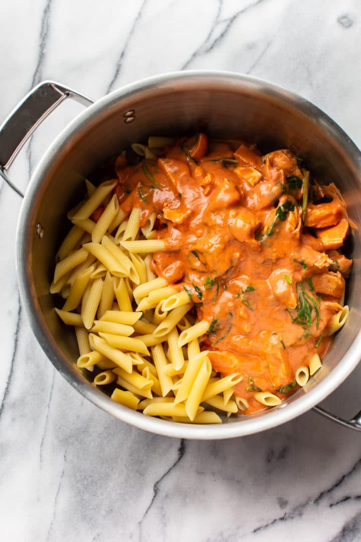 tomato spinach chicken pasta in a pot with cooked penne (ready to be tossed with pasta)