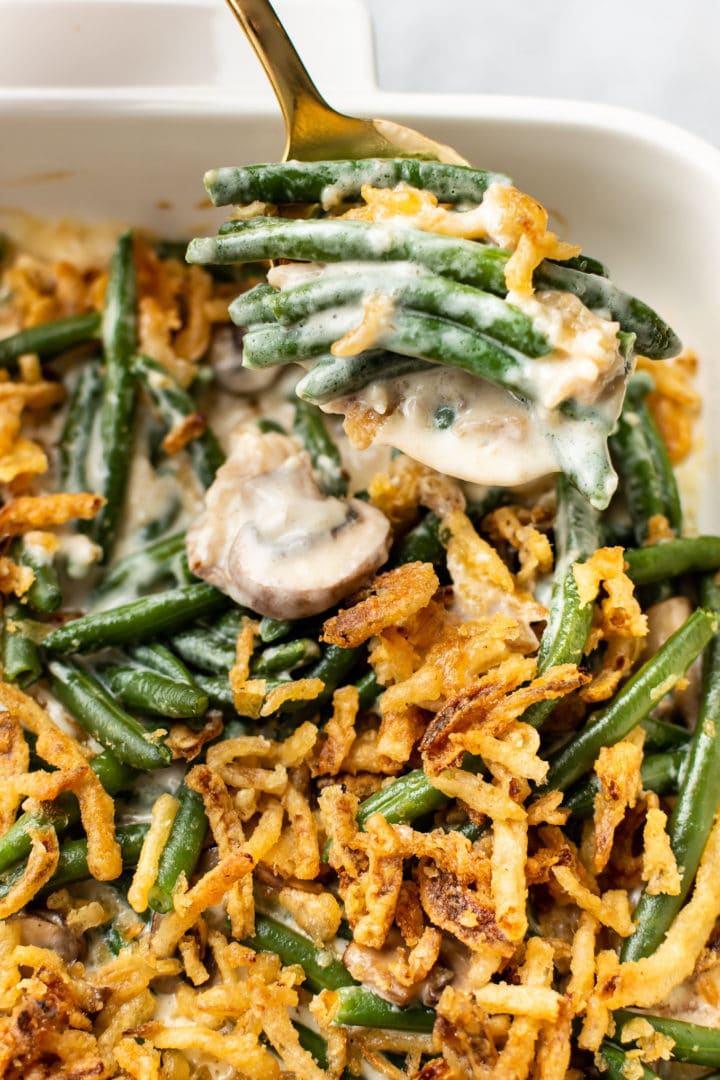 close-up of green bean casserole (from scratch) in a white baking dish with a spoonful being taken out