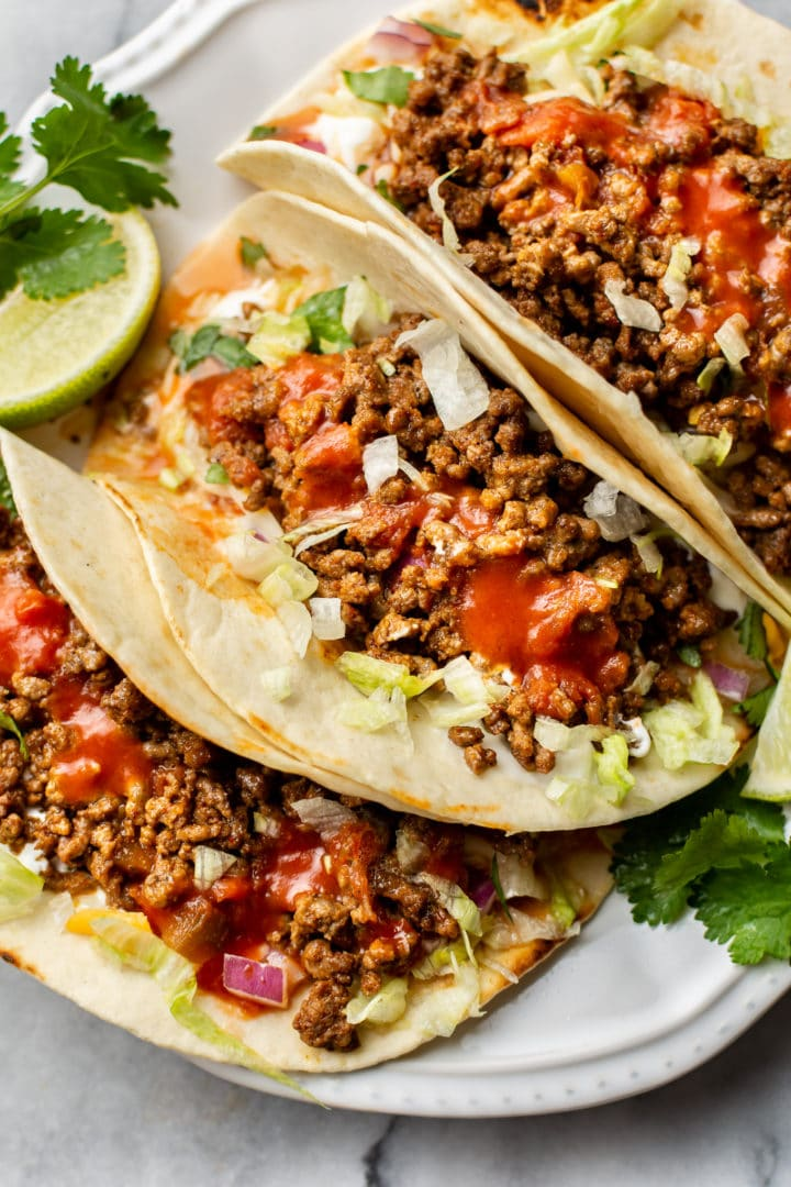 ground beef taco recipe (the best ground beef tacos loaded with toppings on a white plate)