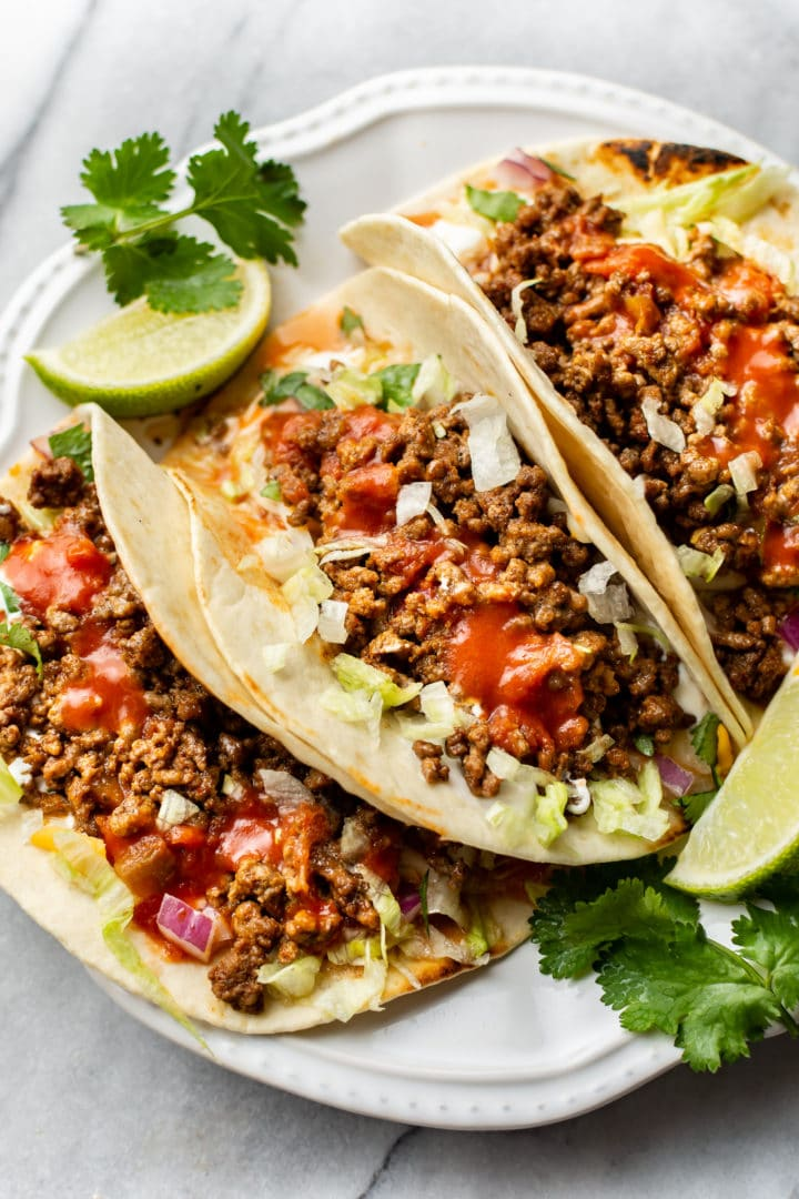 close-up of three ground beef tacos on a white plate with extra lime wedges and cilantro