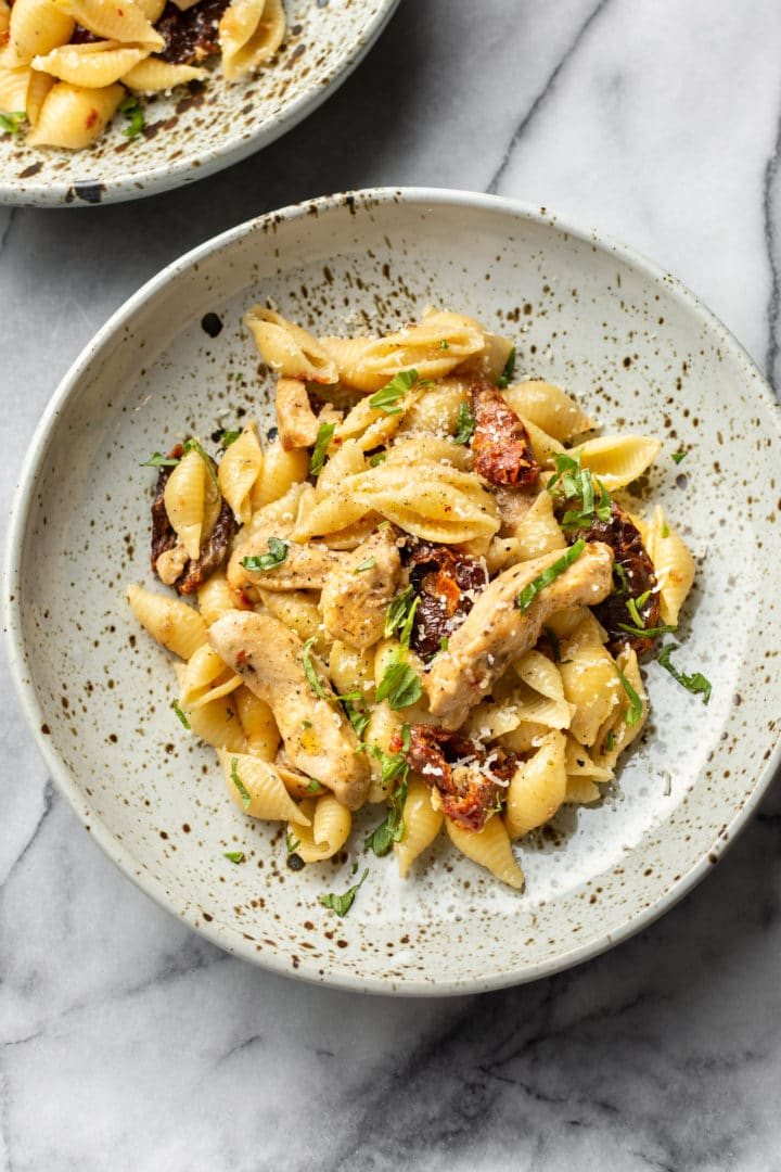 sun-dried tomato chicken pasta in two shallow bowls