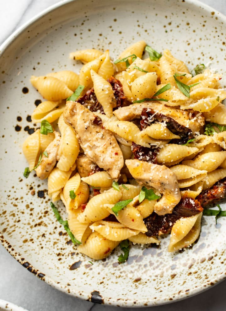 sun-dried tomato chicken pasta close-up in a shallow bowl
