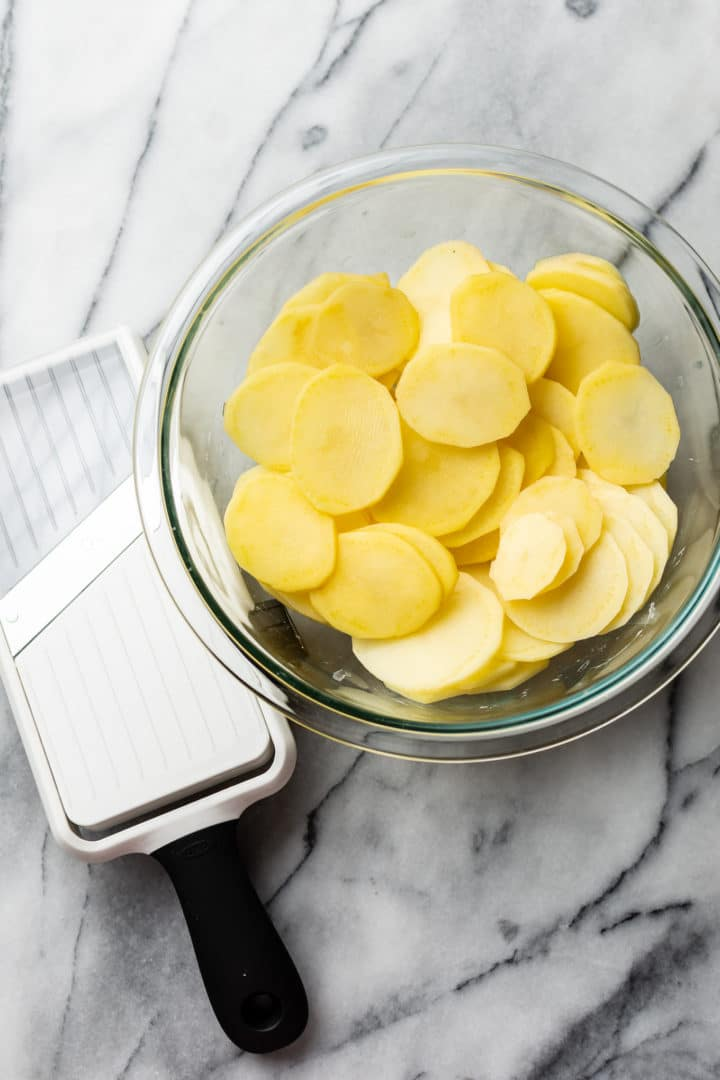 mandoline slicer and sliced potatoes in a glass bowl