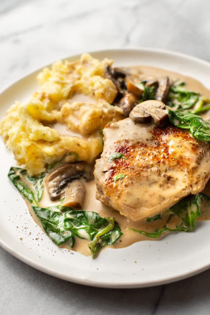 creamy pork chops with spinach and mushrooms on a plate with mashed potatoes
