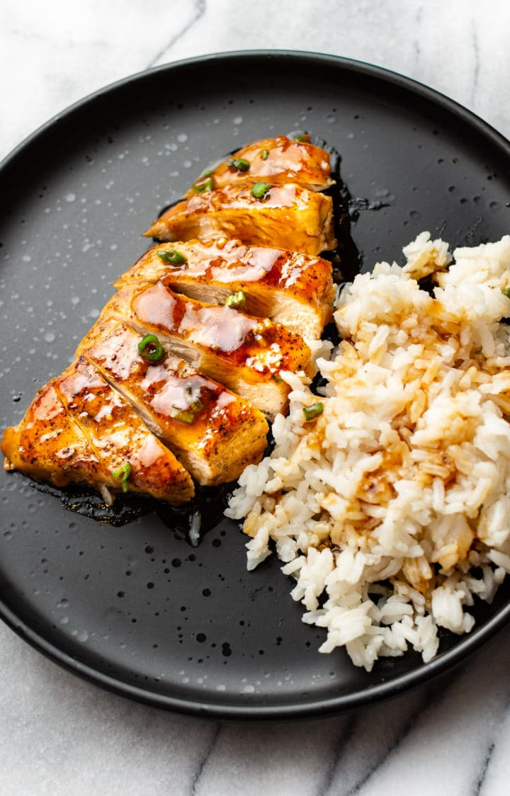 sliced honey garlic chicken breast on a plate with rice and sauce