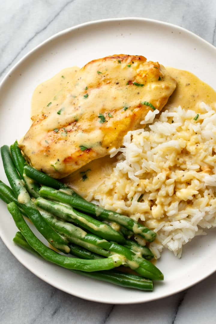 lemon pepper chicken on a plate with green beans and rice