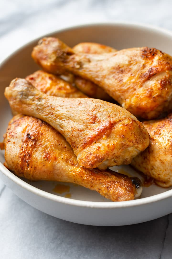 close-up of baked chicken legs (drumsticks) stacked in a bowl