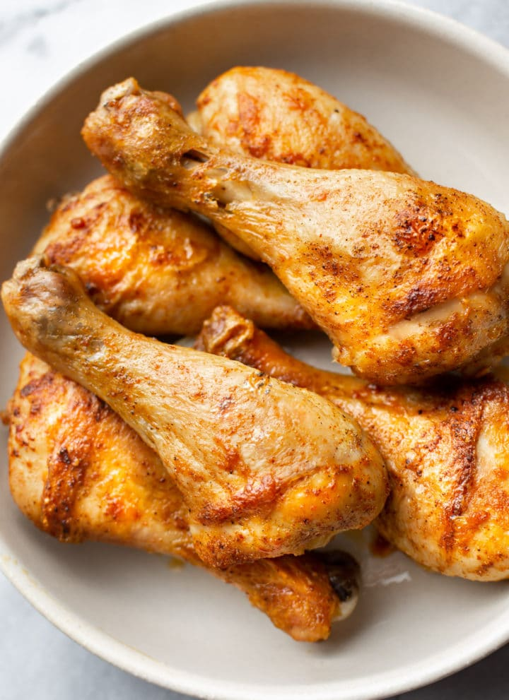 stacked baked drumsticks in a bowl