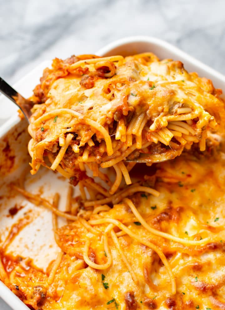close-up of baked spaghetti in a casserole dish being lifted out with a spatula