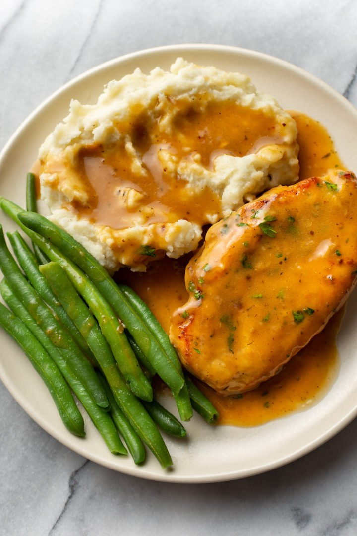 chicken and gravy with mashed potatoes and green beans on a plate