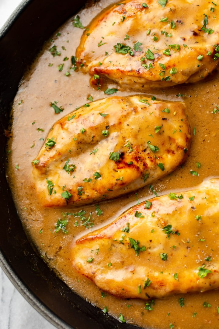 close-up of chicken breasts and gravy in a skillet
