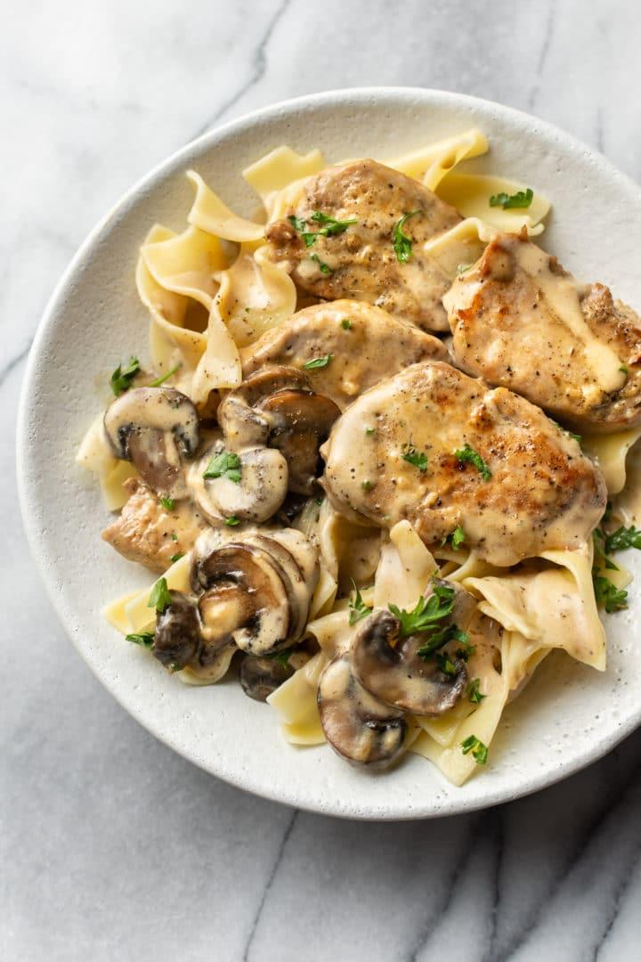 pork tenderloin with creamy mushroom sauce over egg noodles in a shallow bowl