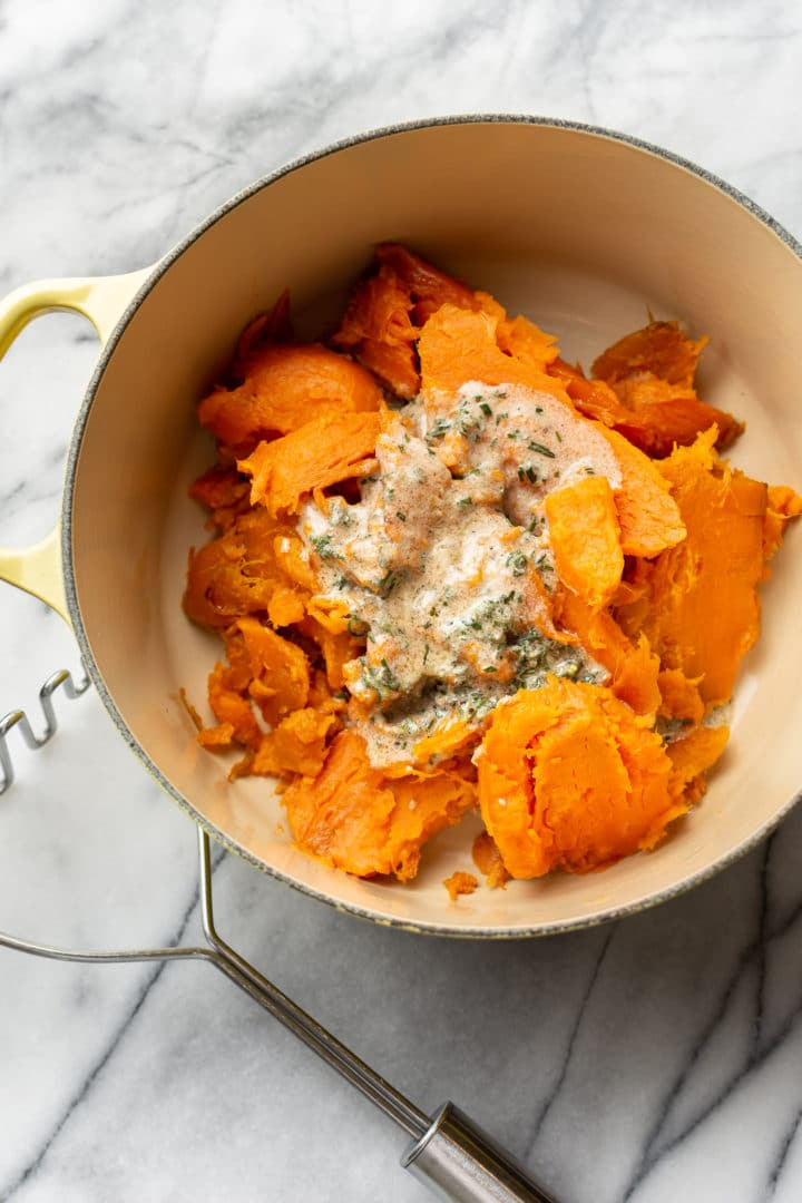 sweet potatoes ready to be mashed in a yellow pot