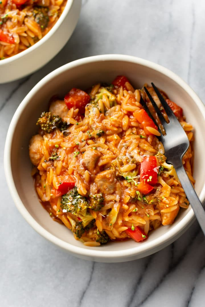 tomato orzo with chicken sausage and peppers in two bowls