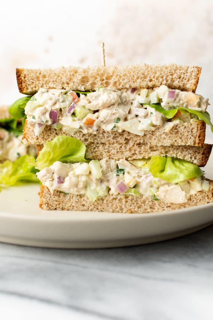 two classic chicken salad sandwiches stacked on top of each other