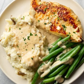 creamy garlic parmesan chicken on a plate with mashed potatoes, green beans, and plenty of sauce