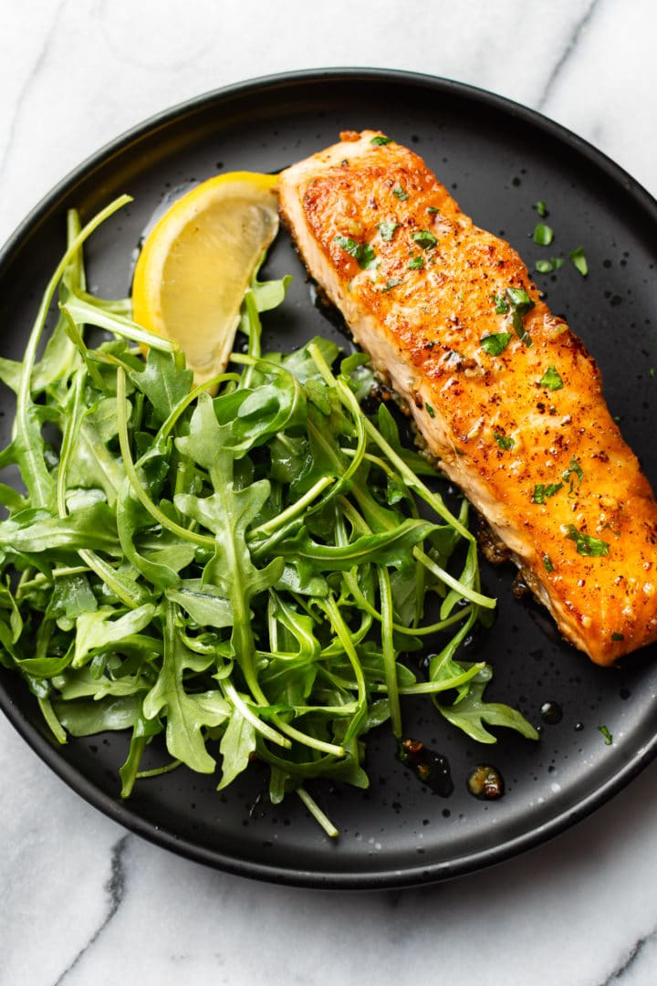 garlic butter salmon on a black plate with arugula salad and a lemon wedge