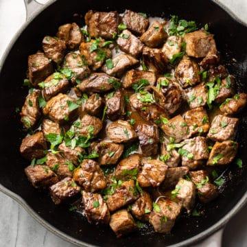 garlic steak bites with parsley sprinkled on top in a skillet