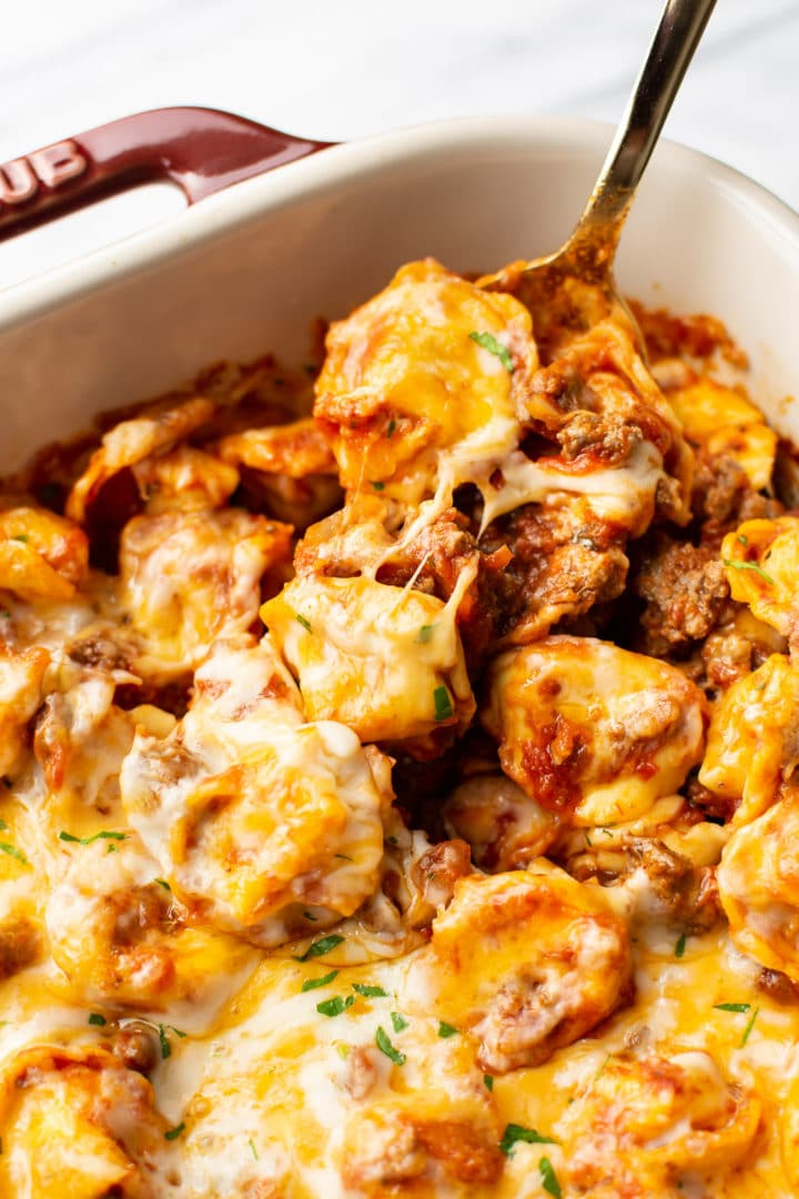 close-up of a spoonful of cheesy baked tortellini in a Staub baking dish