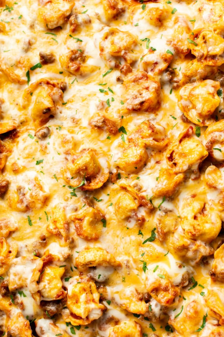 close-up of cheesy baked tortellini with meat sauce