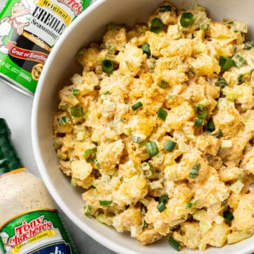 Creole ranch potato salad in a serving bowl with Tony Chachere's Original Creole Seasoning shaker container and Tony's Ranch Dressing bottle