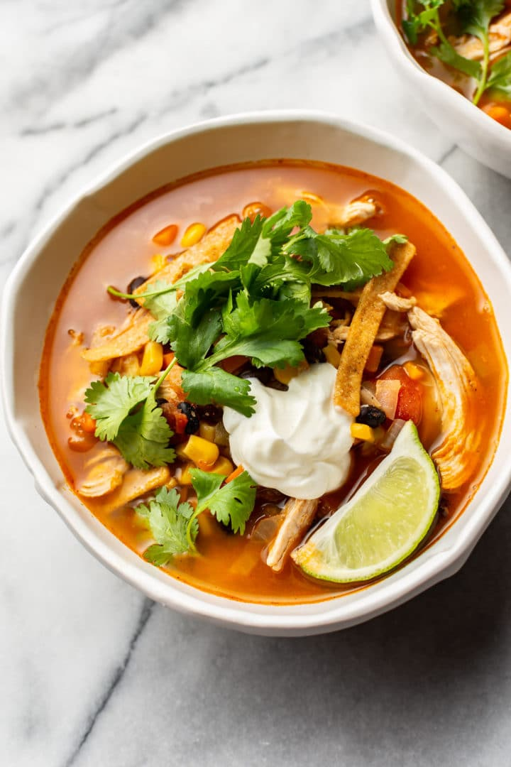Mexican chicken tortilla soup in two white bowls on marble background