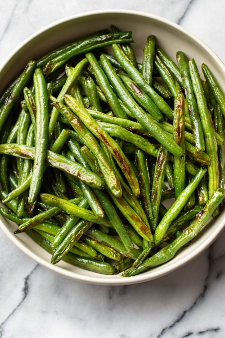 the best roasted green beans in a beige serving bowl