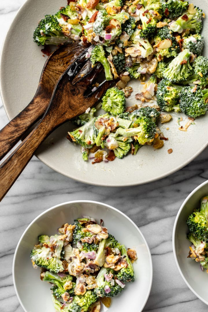 broccoli salad in large serving bowl with wooden tongs and surrounded by two smaller salad bowls with broccoli salad
