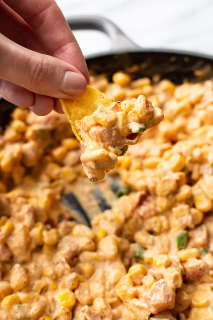 cream cheese corn dip in a skillet being scooped out with a tortilla chip