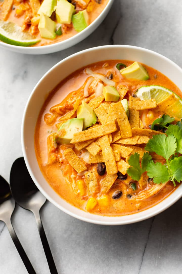 creamy Mexican chicken tortilla soup in two bowls with spoons on the marble background