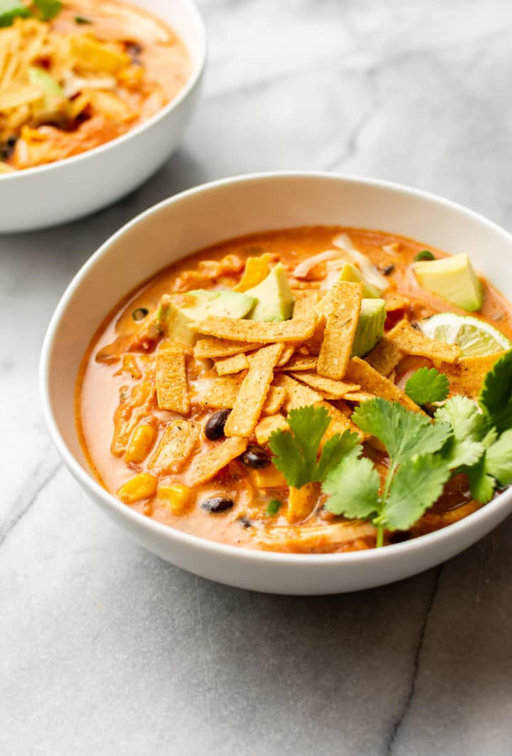 creamy chicken tortilla soup in two white bowls
