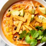close-up of easy creamy chicken tortilla soup loaded with toppings