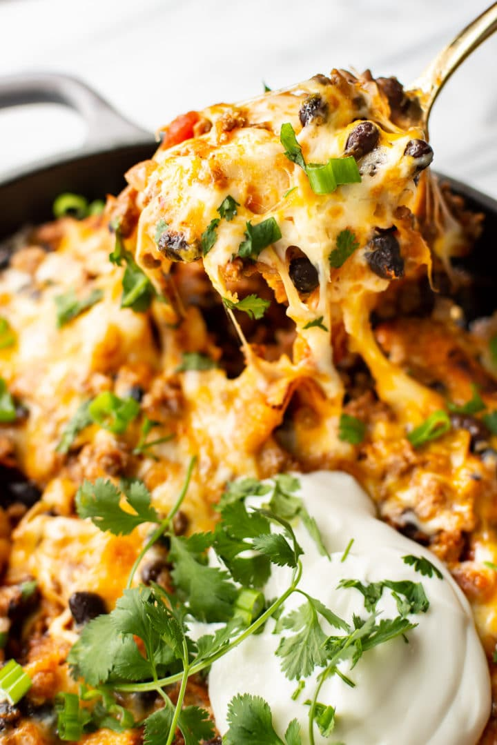 cheesy beef taco skillet close-up with a spoonful being lifted out of the pan