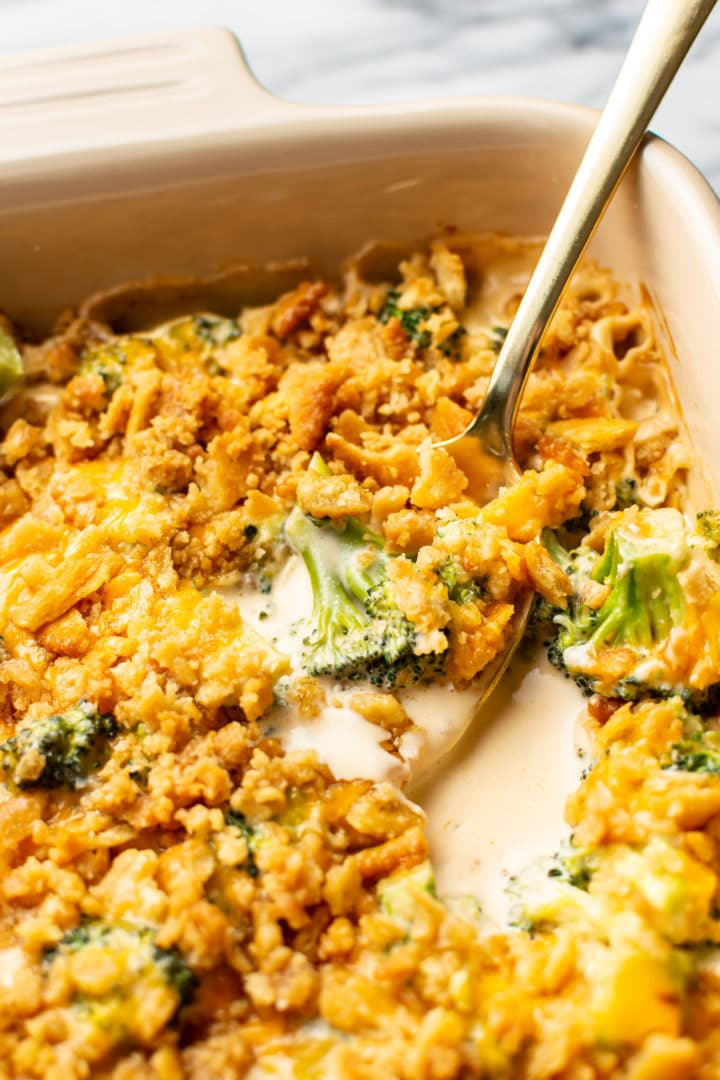 broccoli cheese casserole close-up with a spoonful being lifted out of casserole dish