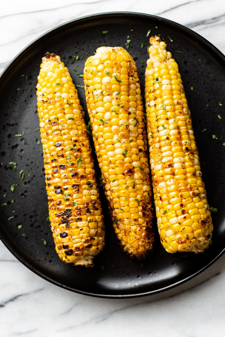 3 cobs of grilled corn on a black plate