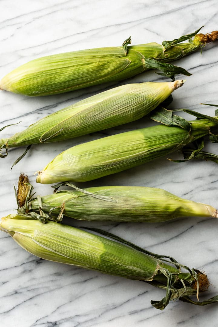 5 ears of corn in their husks