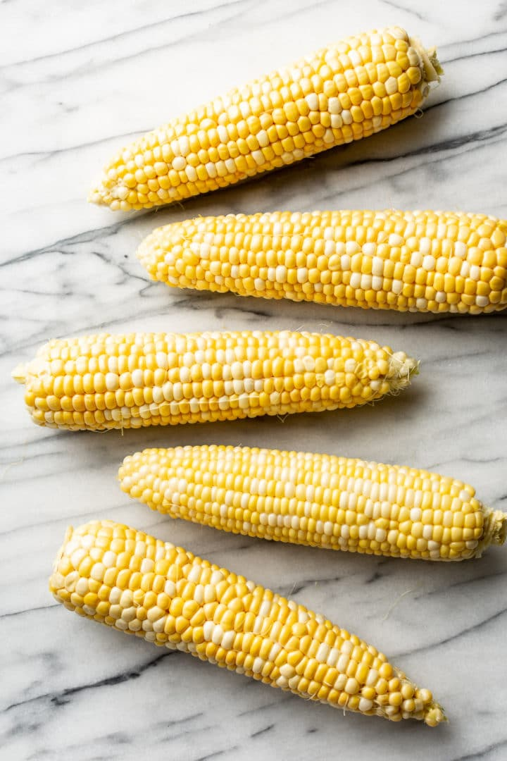 5 ears of husked corn on a marble background