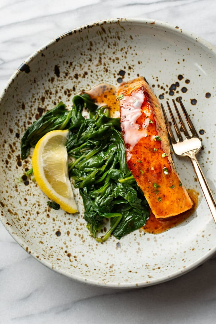 the best brown sugar salmon in a shallow bowl with spinach and a wedge of lemon