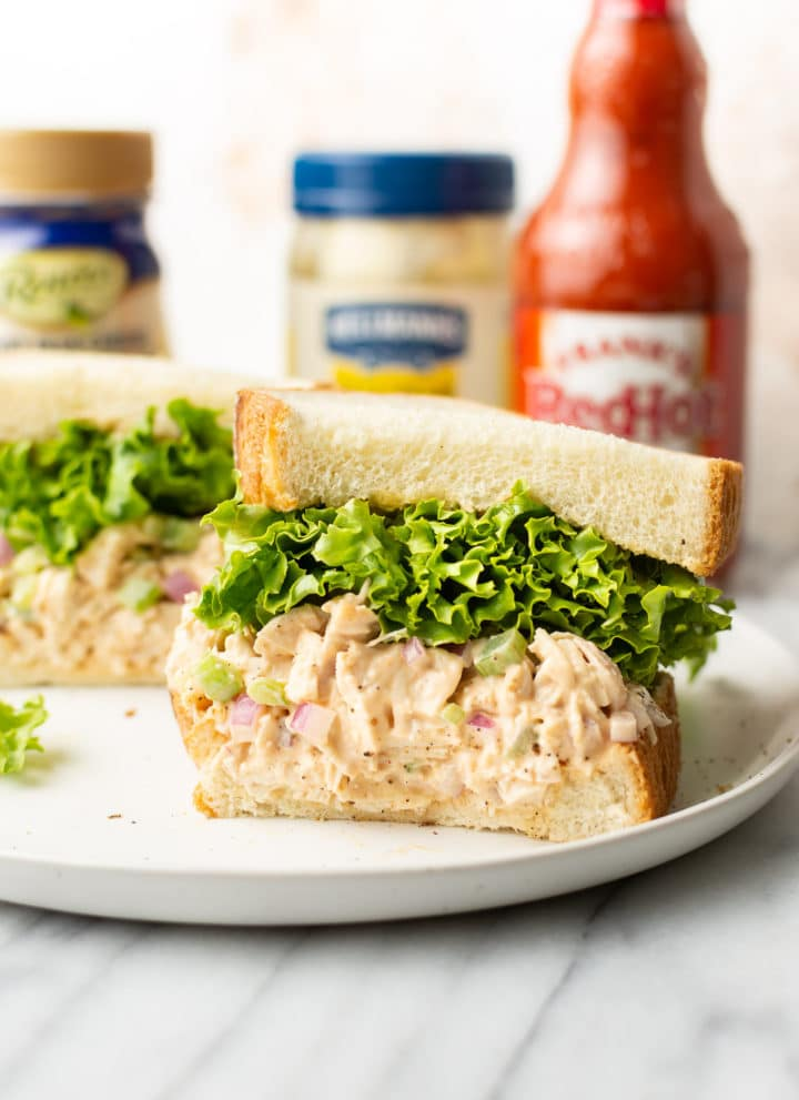 buffalo chicken sandwich cut in half surrounded by Frank's Red hot sauce, blue cheese dressing, and a jar of Hellmann's mayo
