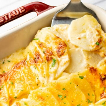 close-up of cheesy scalloped potatoes being lifted out of casserole dish with spatula