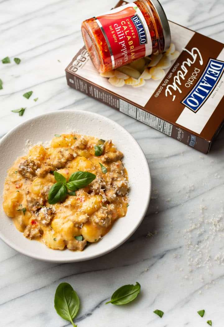 spicy Italian sausage gnocchi in a white bowl surrounded by fresh basil, a package of DeLallo potato gnocchi, and a jar of DeLallo calabrian chili peppers