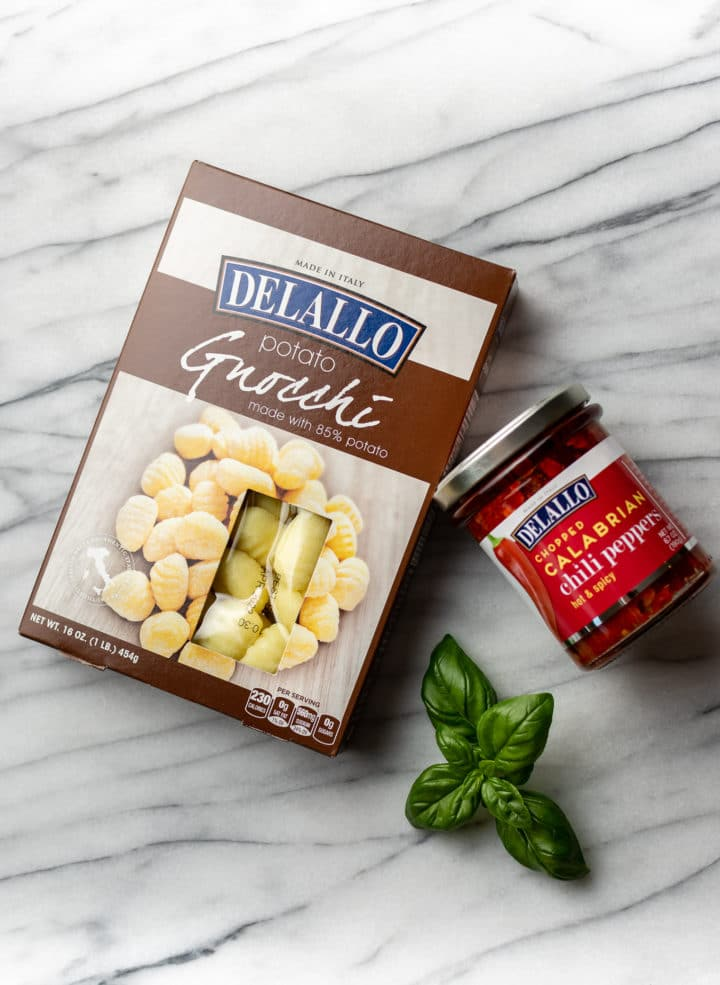 DeLallo potato gnocchi package and a jar of DeLallo chopped calabrian chili peppers in a jar