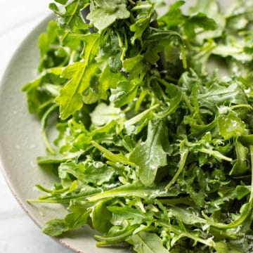 classic parmesan arugula salad being lifted out of a serving bowl with tongs