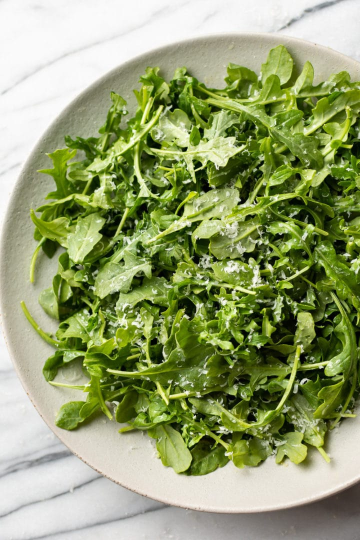 the best arugula salad in a shallow serving bowl