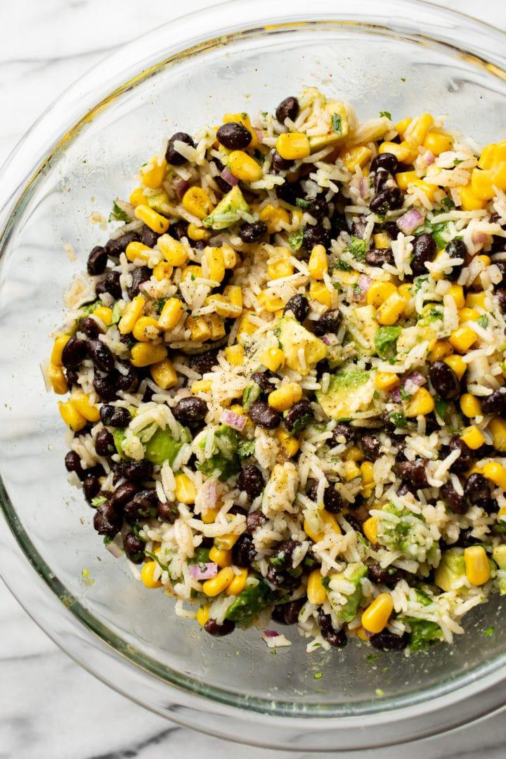 close-up of black bean, corn, avocado salad in a glass prep bowl