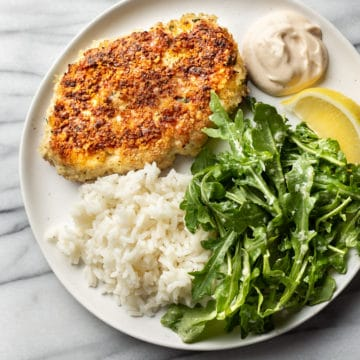 chicken patties on a plate with rice, remoulade sauce, arugula salad, and a lemon wedge