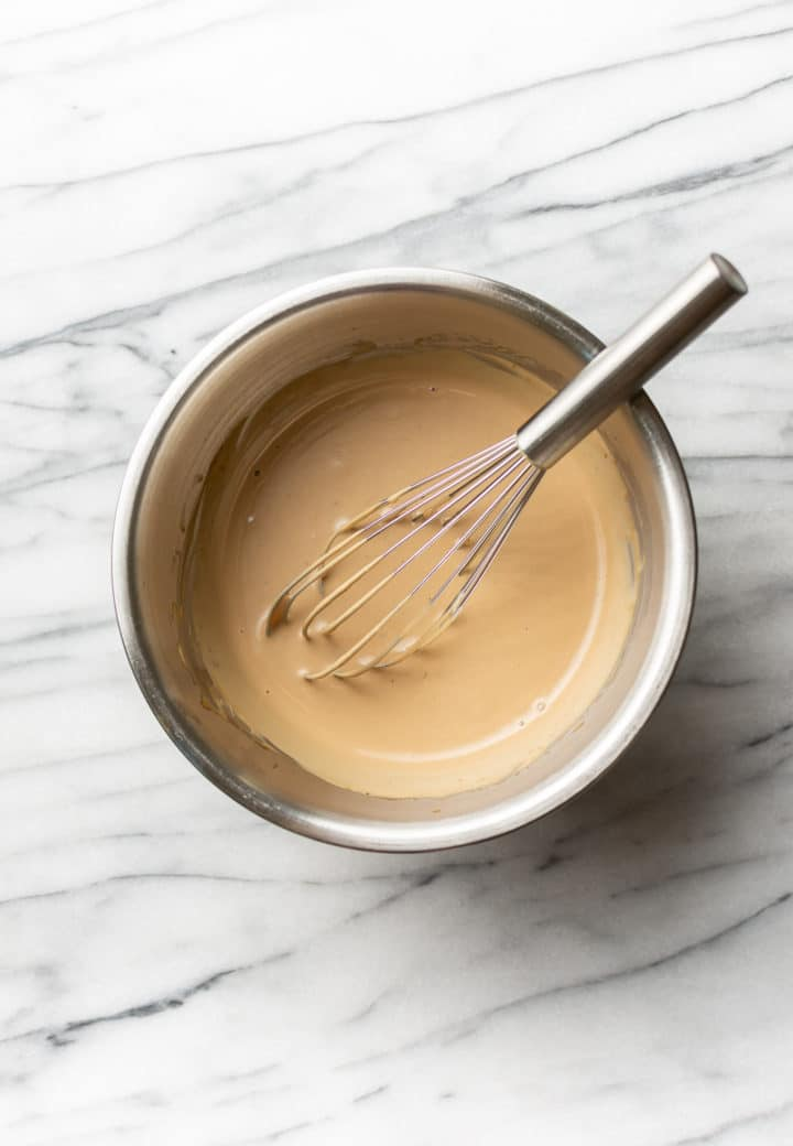 creamy balsamic salad dressing in a metal prep bowl with a whisk